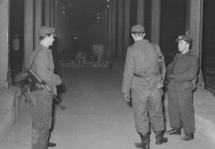 Border soldiers guard  bricklayers who are putting up a barrier wall between the Heinrich-Heine-Strasse and Moritzplatz underground railway stations, 15 Februar 1963