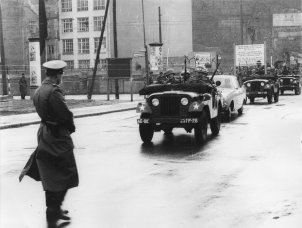US military vehicles protect the entry of a civilian vehicle into East Berlin via the border crossing Checkpoint Charlie, October 1961