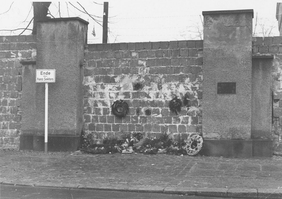 West Berliners, who are no longer permitted to enter St. Hedwig's Cemetery on Liesenstrasse, lay down their wreathes at the walled-up cemetery entrance, 26 November 1961
