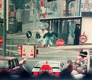 East Berliners jump over the barrier